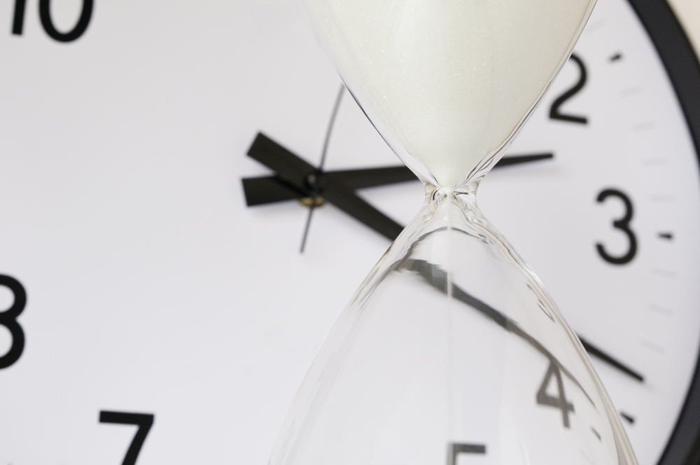 Two measurements of time White sand falling inside hourglass, with round analog clock in  background (focus on neck of hourglass), shallow depth of field